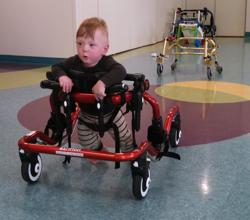 Jax in a gait trainer at Physical Therapy. This is not something he will have to use regularly, but it helps his therapist get an unobstructed view of Jax's feet as he tries to stand and walk.